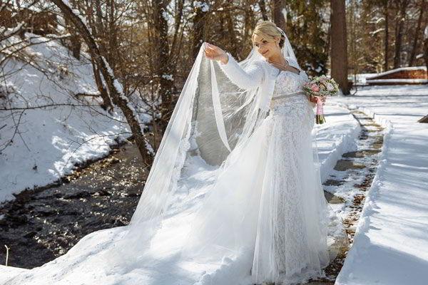 Braut am Flussufer mit Brautkleid im Winter
